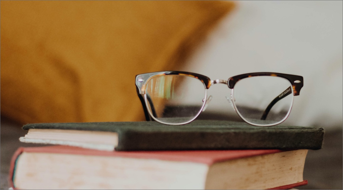 a pair of glasses purched on a stack of books