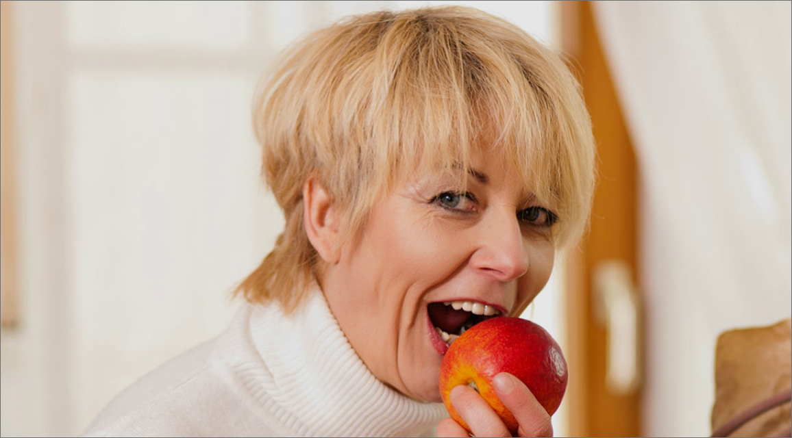 A stylish older woman takes a bite of an apple